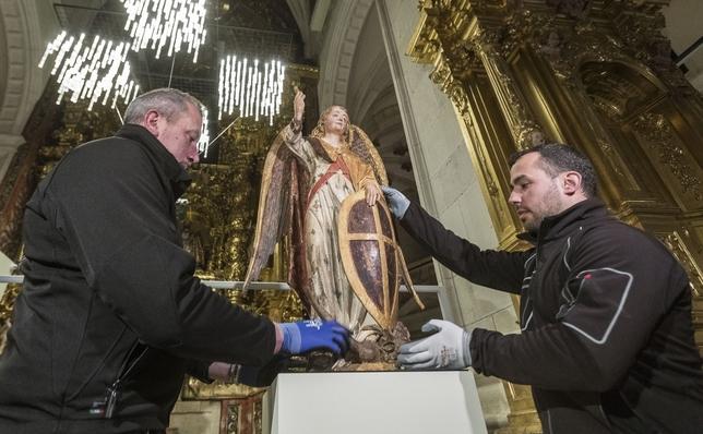Dos trabajadores colocan un arcángel del escultor Alejo de Vahía, procedente del Museo de Becerril de Campos (Palencia).  Alberto Rodrigo