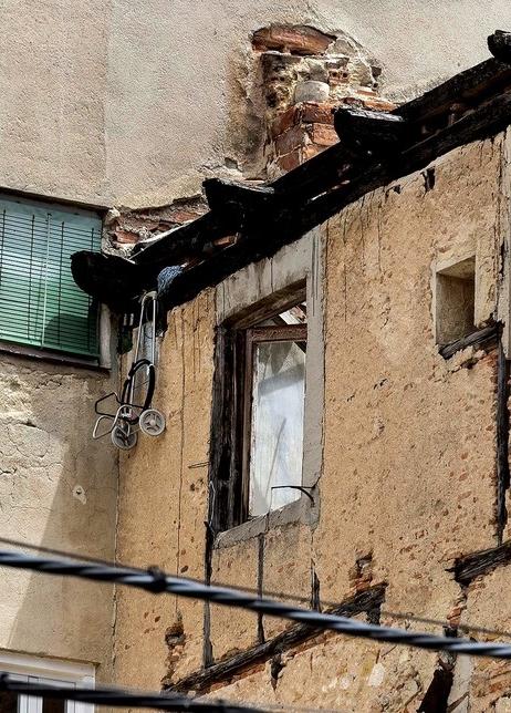 La estructura metálica de un carrito de la compra cuelga de lo alto de la fachada de la Casa Buitrago.  Rosa Blanco
