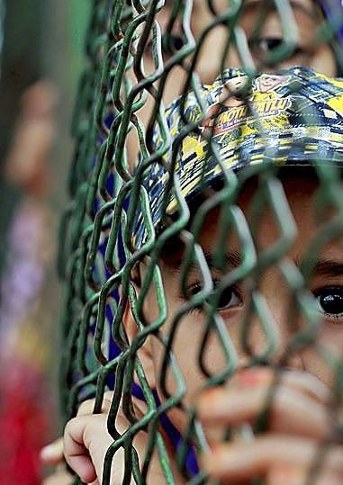 Un niño mira a través de una verja en la región.