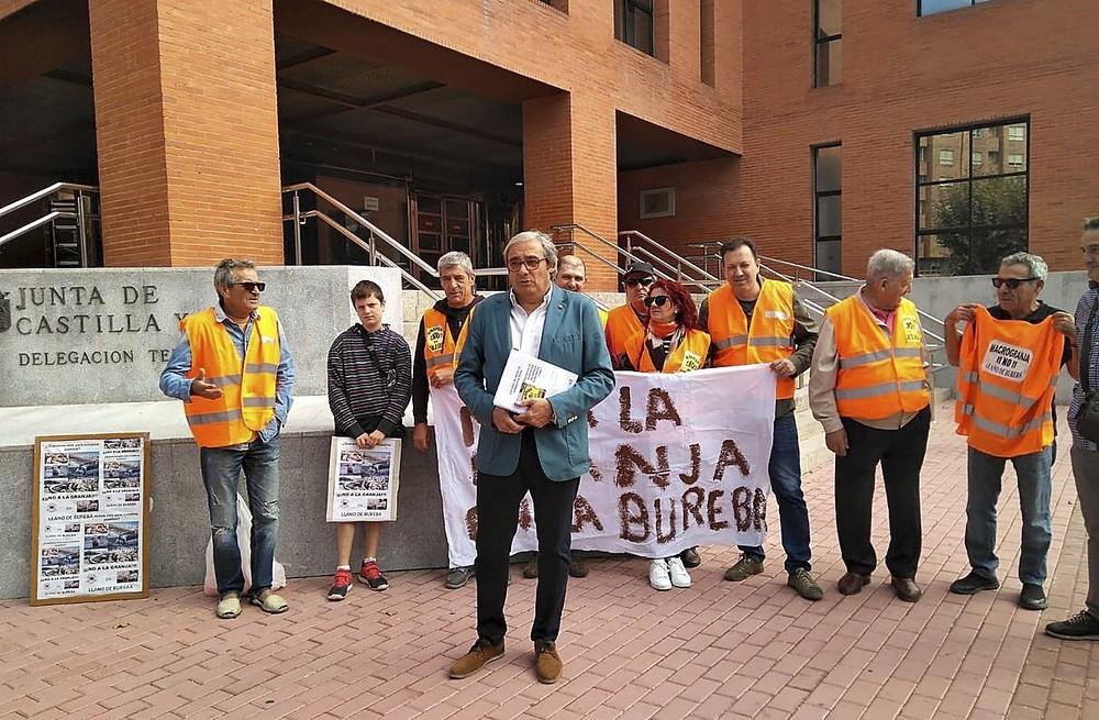 El portavoz de Granja No, David Martínez, acompañado de vecinos de Llano antes de entregar las alegaciones en la Junta.