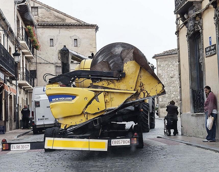 Un vehículo de transporte especial atraviesa Turégano mientras una mujer de avanzada edad se refugia en la acera.