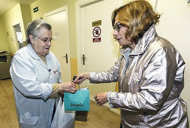 Una voluntaria de Cáritas recibe una donación para la tienda de la ONG. Rosa Blanco