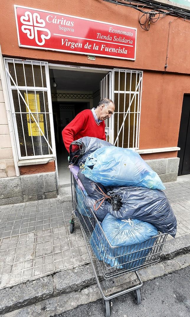 Un voluntario ayuda a introducir en la sede con un carrito varias bolsas repletas de ropa.  Rosa Blanco