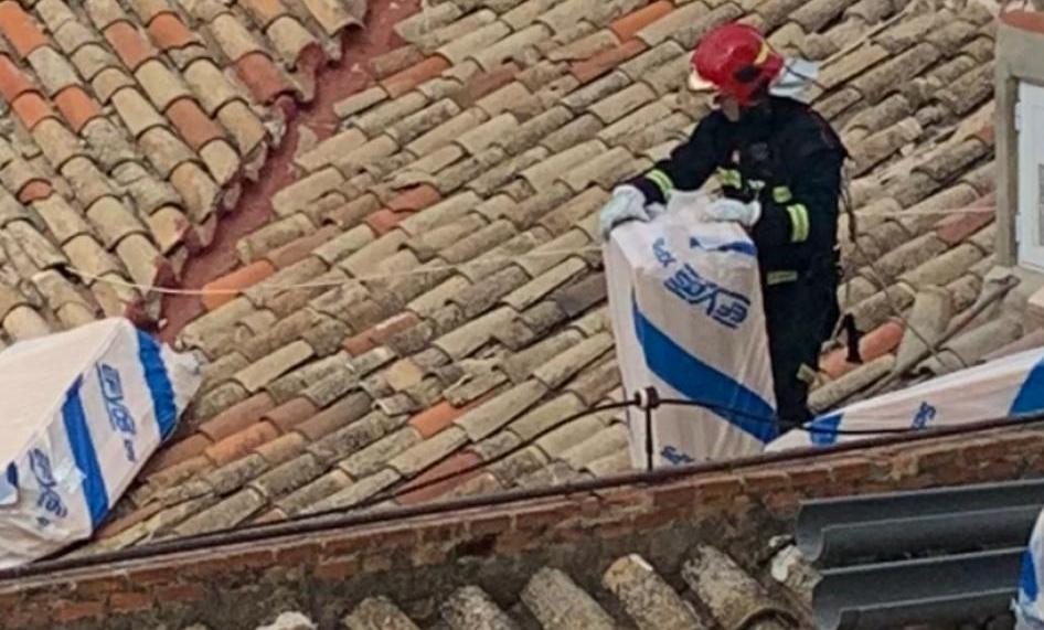 Los bomberos retiran objetos caidos en un tejado de la calle Concepción esta mañana