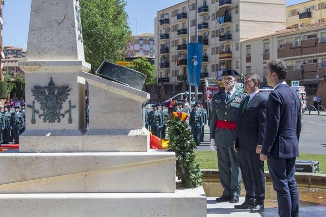 El presidente Page, entre el delegado del Gobierno y el general Llamas, depositando la corona de flores en honor a los caídos.
