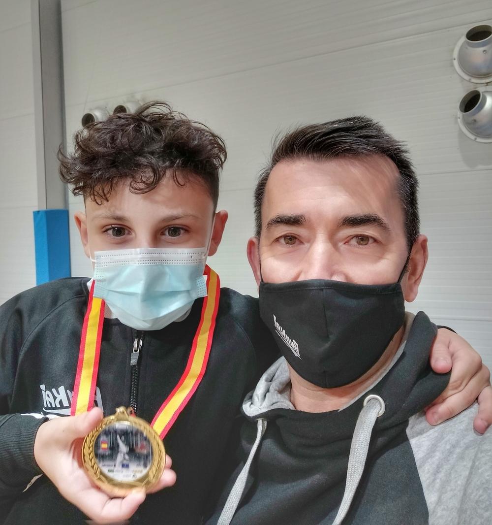 Óscar Heredia muestra su medalla junto al técnico Ángel Jiménez.