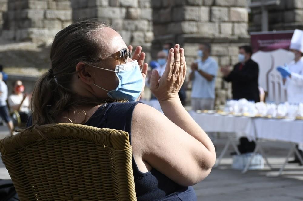 Una de las sanitarias participantes aplaude en el almuerzo que se ha celebrado después a los pies del Acueducto.