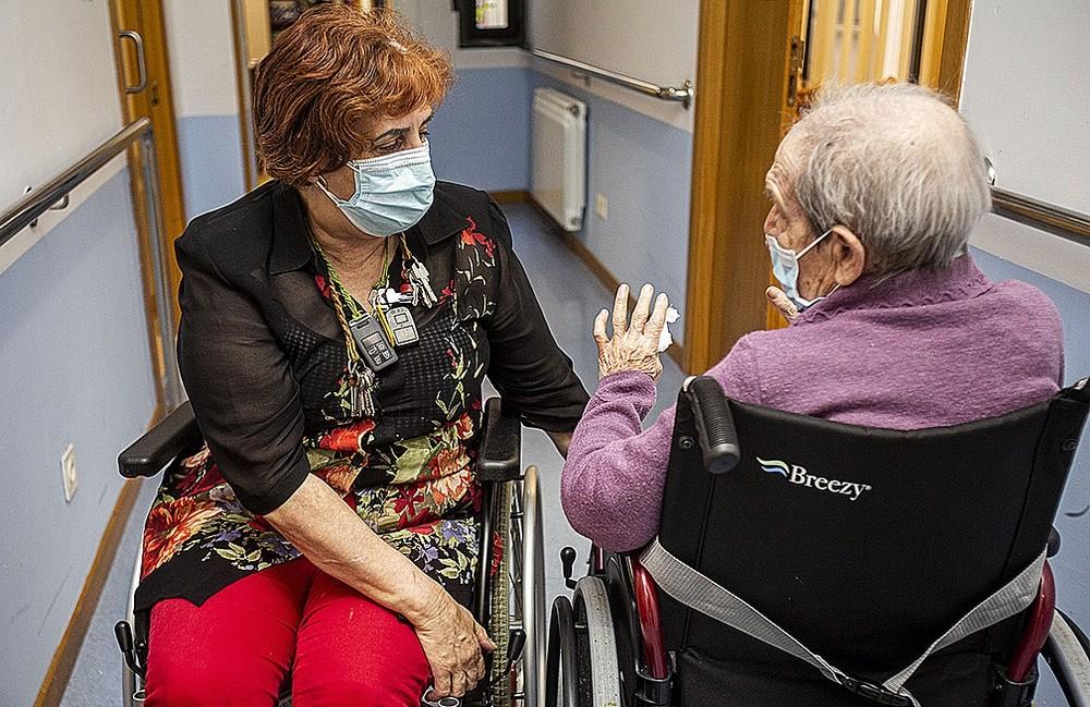 Una trabajadora, con la tibia rota, charla con Mariluz en el pasillo