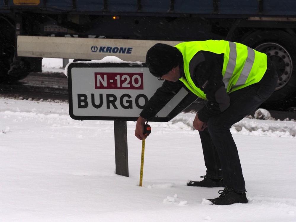 Un camionero saca el metro para medir la capa de nieve caída sobre la N-120.