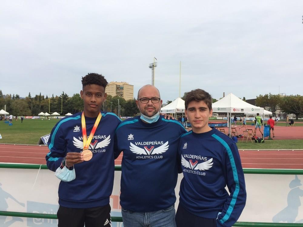 Asabu Pines muestra su medalla junto a su técnico, Ángel Sánchez, y su compañero de equipo Iván Rivero, que fue duodécimo en triple salto.