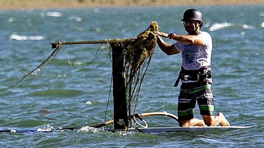Eduardo Navarro limpia de algas la quilla foil de su tabla.