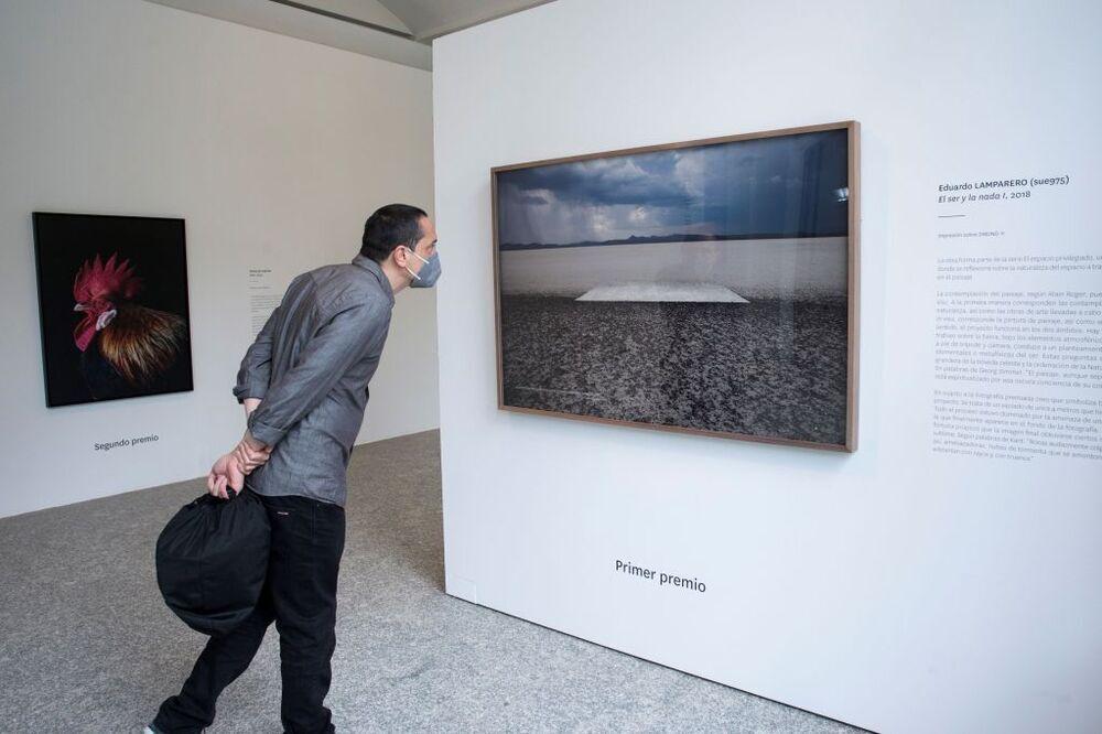 Un hombre observa los trabajos de los 'Premios Fotografía de la Fundación ENAIRE' en el Real Jardín Botánico de Madrid y que forma parte de PHotoESPAÑA.