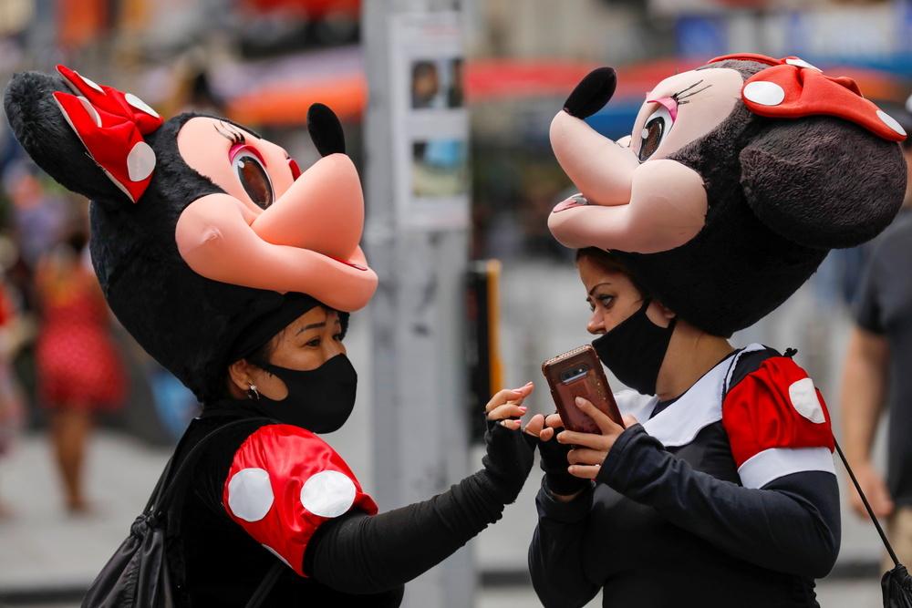 Dos mujeres con mascarilla disfrazadas de Minnie Mouse en los alrededores de Times Square.