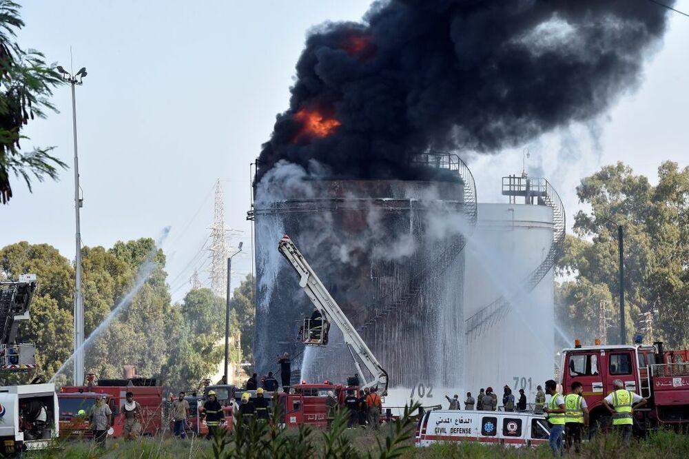 Los bomberos extinguen las llamas en uno de los tanques de combustible que contienen gasolina en Zahrani
