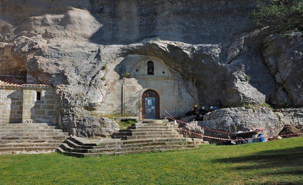 La tumba está empotrada en la roca junto a la entrada a la ermita de San Tirso y San Bernabé.
