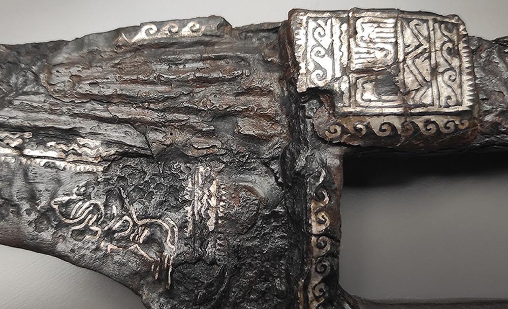 Detalle de la falcata, con los motivos damasquinados de plata.