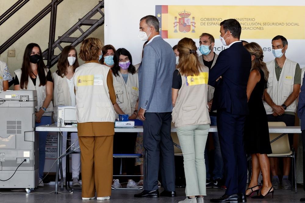 El Rey Felipe VI y el presidente del Gobierno, Pedro Sánchez, conversan con varias personas durante su visita este sábado al centro de acogida temporal instalado en la base de Torrejón de Ardoz