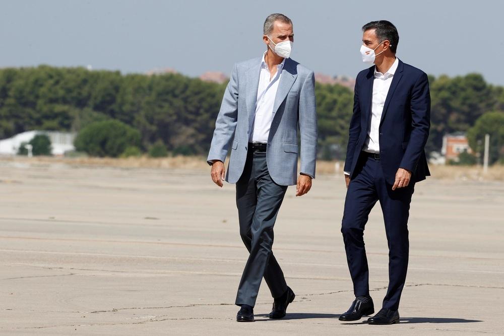 El Rey Felipe VI y el presidente del Gobierno, Pedro Sánchez, conversan durante su visita este sábado al centro de acogida temporal instalado en la base de Torrejón de Ardoz