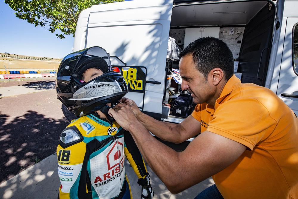 Tomás García, padre de Alonso, le ayuda a colocarse el casco.