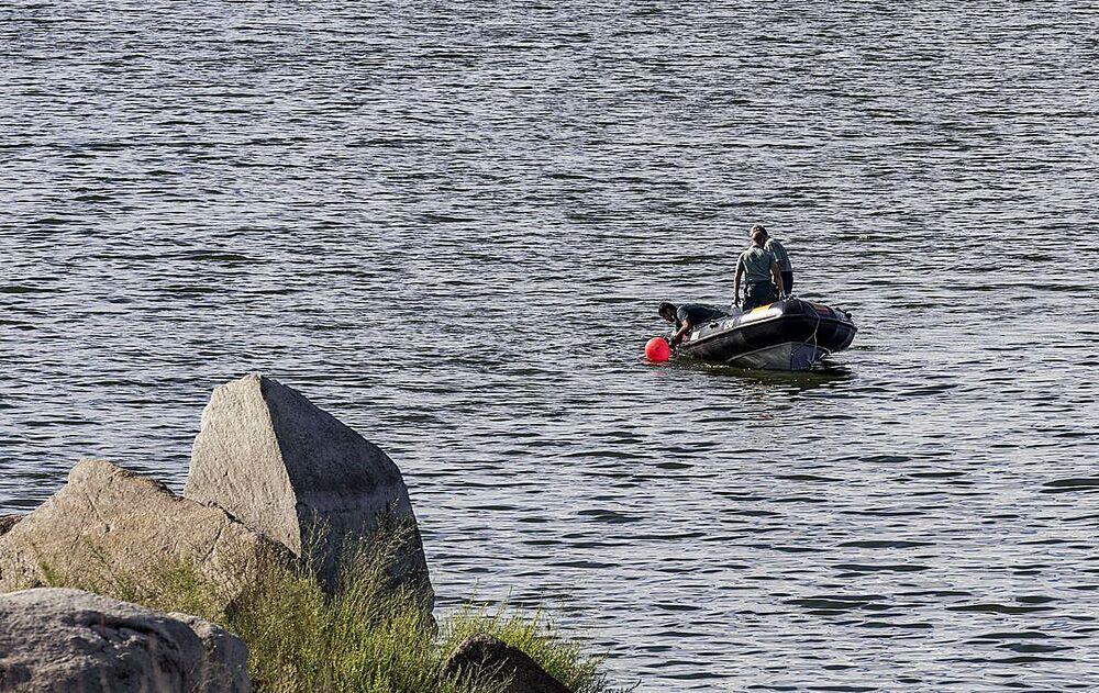 Los especialistas de la Guardia Civil rastrean las aguas con una embarcación, ayer en el embalse de Guajaraz.