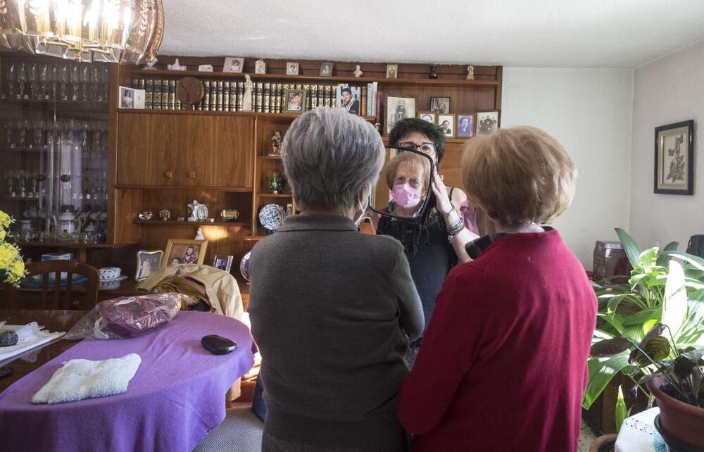 La peluquera, que es acogida en cada casa casi como un miembro de la familia, mostrando a dos de sus clientes el resultado.