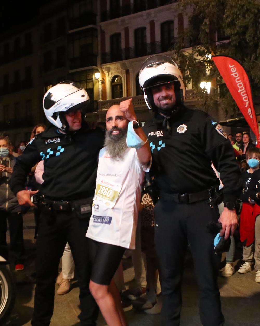 El atleta con discapacidad Paco Pérez posa con los policías locales que le escoltaron durante el recorrido tras cruzar la meta.
