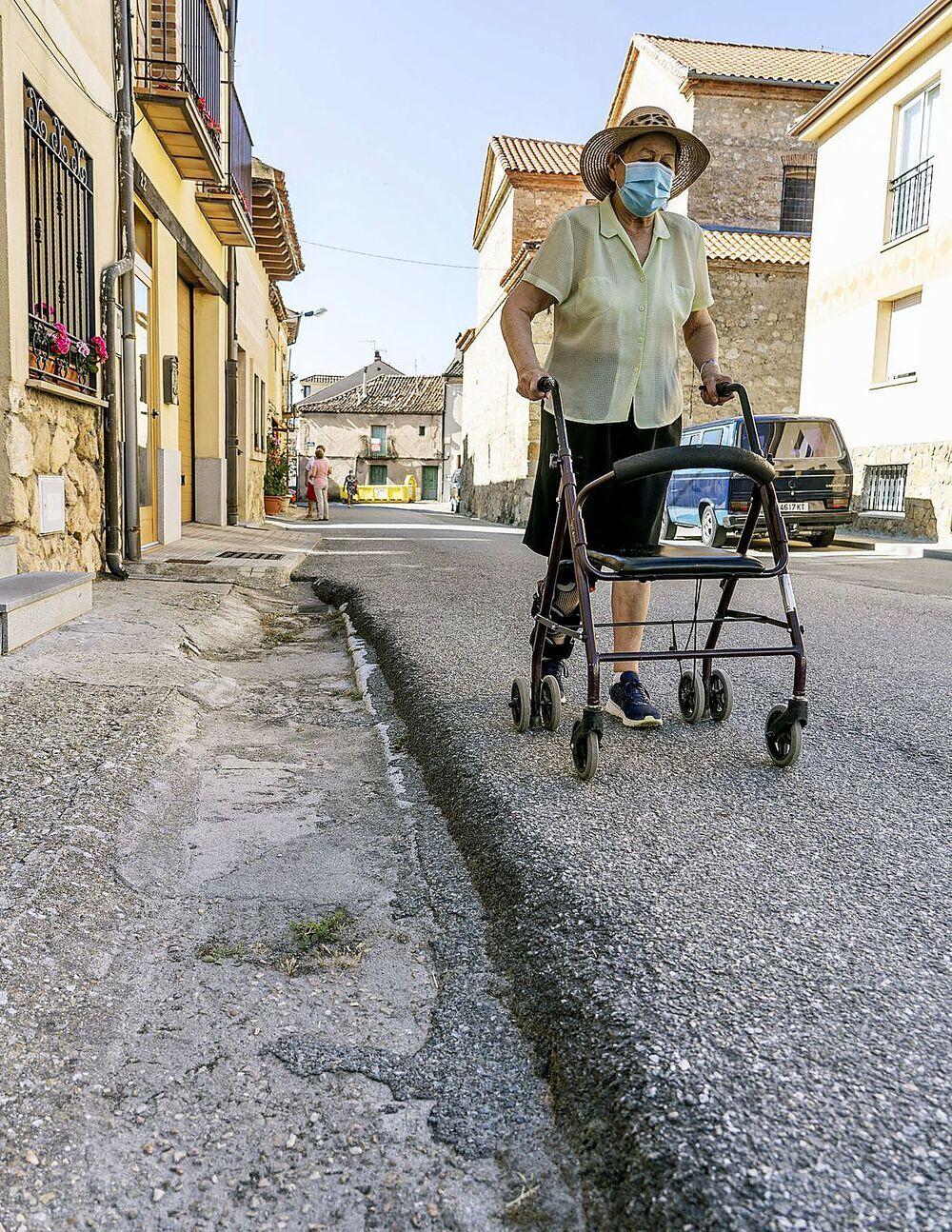 La octogeneria Isabel Ceballos, debe circular por la calzada en la calle Real Alta, ante la ausencia de una acera transitable.