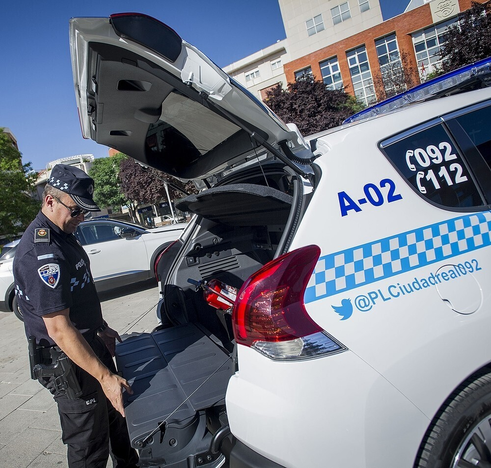 Un agente de la Policía Local revisa el maletero de su vehículo oficial
