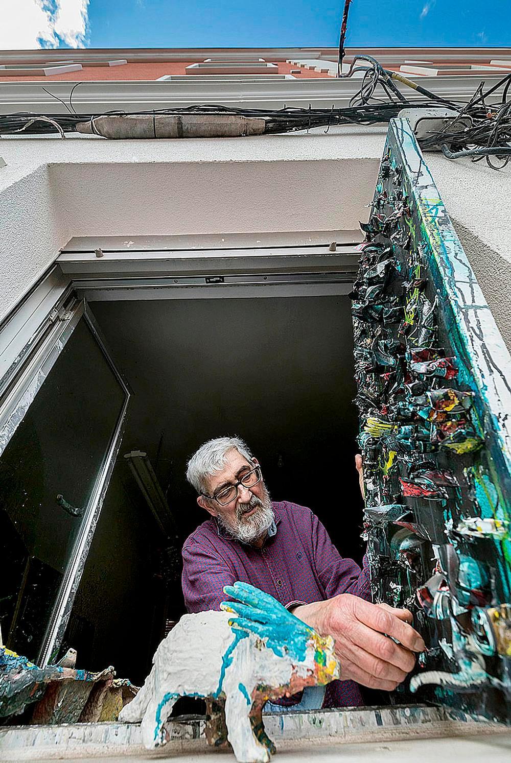 Juan, con una de sus obras asomado a la ventana de su estudio.
