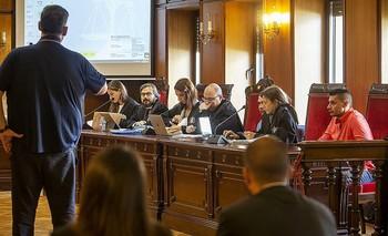 Los dos acusados (de naranja y azul), sentados junto a los letrados y la fiscal, escuchan la declaración del dueño del pub.