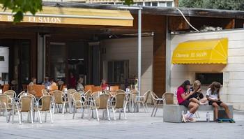 Jóvenes consultan el móvil en una terraza de Palencia.