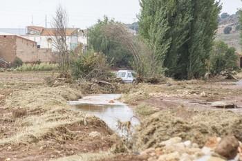 El agua entró en tromba en la localidad. Al fondo, la furgoneta en la que quedó atrapado un conductor.