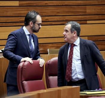 El procurador de Vox Jesús García-Conde (I) conversa con el 'popular' Pablo Trillo durante el Pleno de las Cortes.