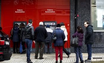 Una decena de personas esperando para hacer gestiones en un cajero automático de Ibercaja en Gamonal.