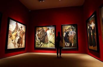 Un visitante recorre las salas de la galería con los lienzos del valenciano