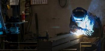 Un hombre trabaja con un soplete en el interior de una empresa de la Comunidad.