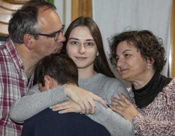 Andrea, acogida por Nuria y Juan María con 12 años (ahora tiene 20 años), abraza al último menor llegado a la casa familiar.