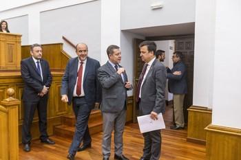 El presidente de Castilla-La Mancha saluda al consejero de Agricultura al entrar en el salón de plenos.