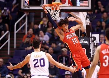 El pívot de los New Orleans Pelicans, Jaxson Hayes (d), se cuelga del aro ante Dario Saric, de los Phoenix Suns