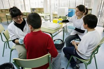 Imagen de archivo de varios niños de un colegio mientras son vacunados frente a la hepatitis A.