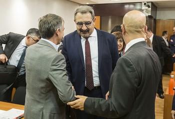 El consejero de Sanidad, Jesús Fernández Sanz, saludando al portavoz socialista a su entrada en la Comisión. /