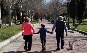 Dos abuelos pasean a su nieto por la calle.