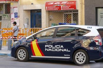 Imagen de un coche de la Policía Local que custodia el edificio confinado.
