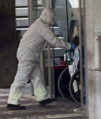 Un sanitario accede a un hospital con una paciente en silla de ruedas.