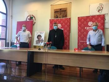 El obispo y responsables de Cáritas guardan un minuto de silencio por los fallecidos del COVID-19.