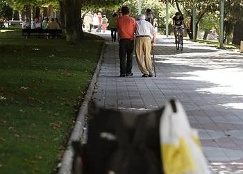 Un anciano con movilidad reducida pasea del brazo de un familiar
