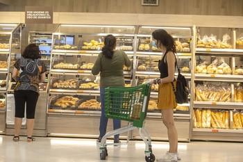 Imagen de varios clientes comprando en la zona de panadería del interior de un supermercado