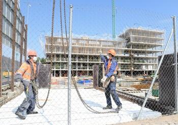 Dos empleados de la construcción trabajan a mediado de abril en la construcción de un edificio.