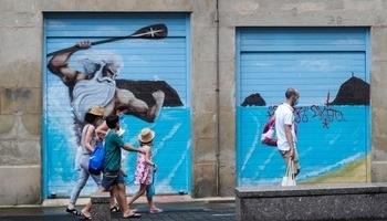 Unos turistas pasan junto a un mural en la Parte Vieja de San Sebastián.