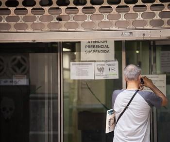 Un hombre toma nota de los horarios de la Oficina de Empleo de Logroño.